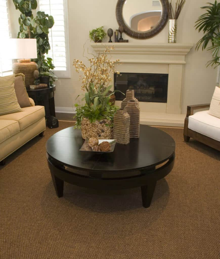 A round coffee table sits on a jute rug in this living room offering a fireplace that's accented with chrome vase and round mirror.