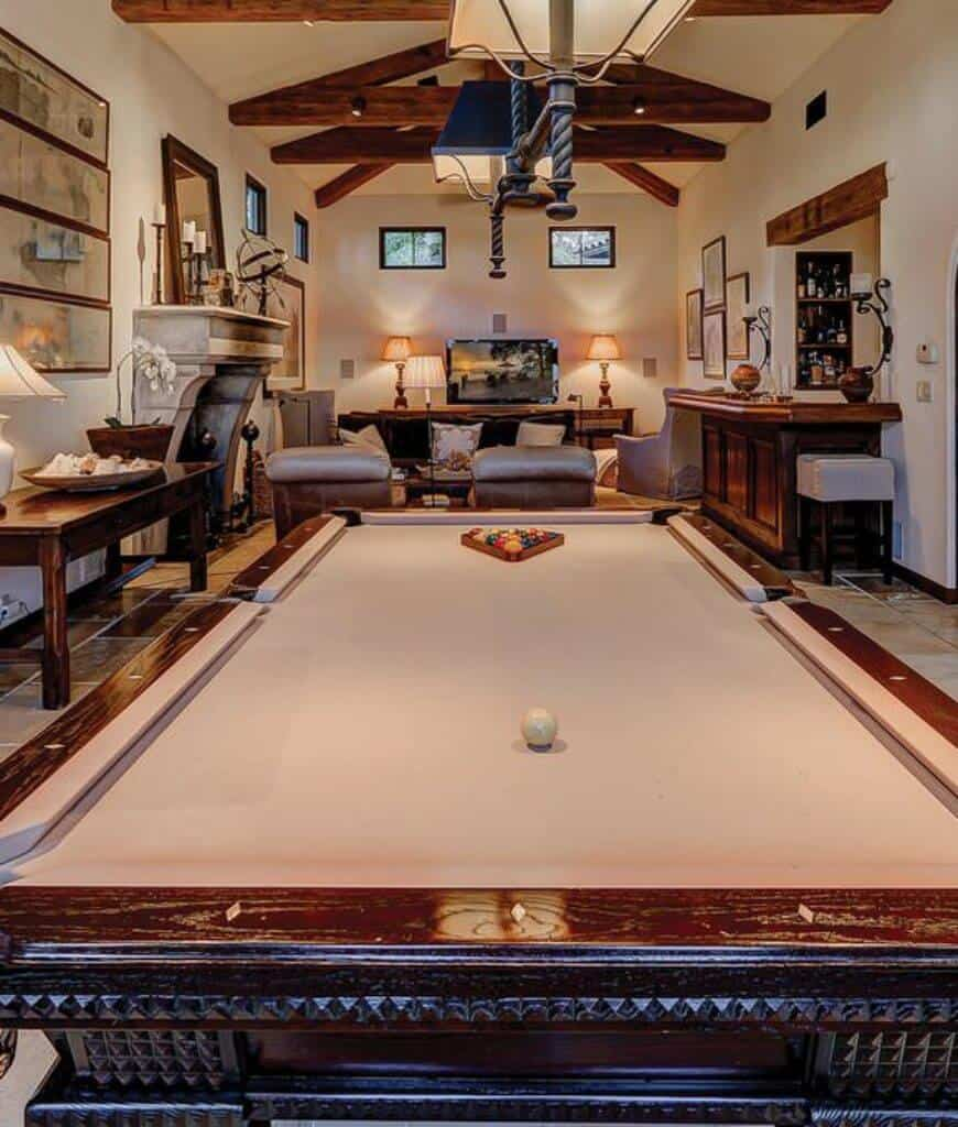 Long and narrow family room furnished with wooden tables and gray seats. It has a stone fireplace and a bar area along with a pool table that blends well with the tiled flooring.