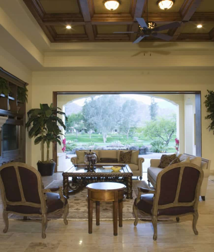 Tropical living room with a lovely green outdoor view featuring a marble flooring and coffered ceiling fixed with flush mount and recessed lights.
