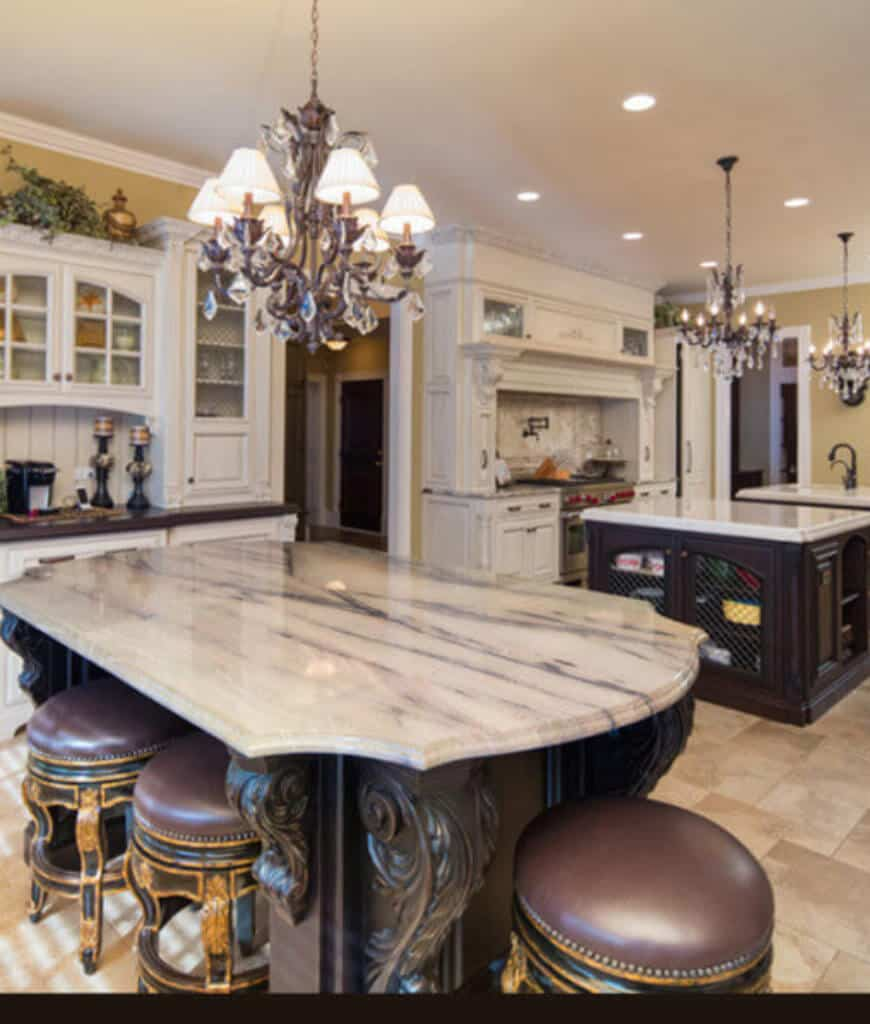 Yellow kitchen with white cabinetry and triple dark wood kitchen islands over limestone flooring lighted by classic chandeliers.