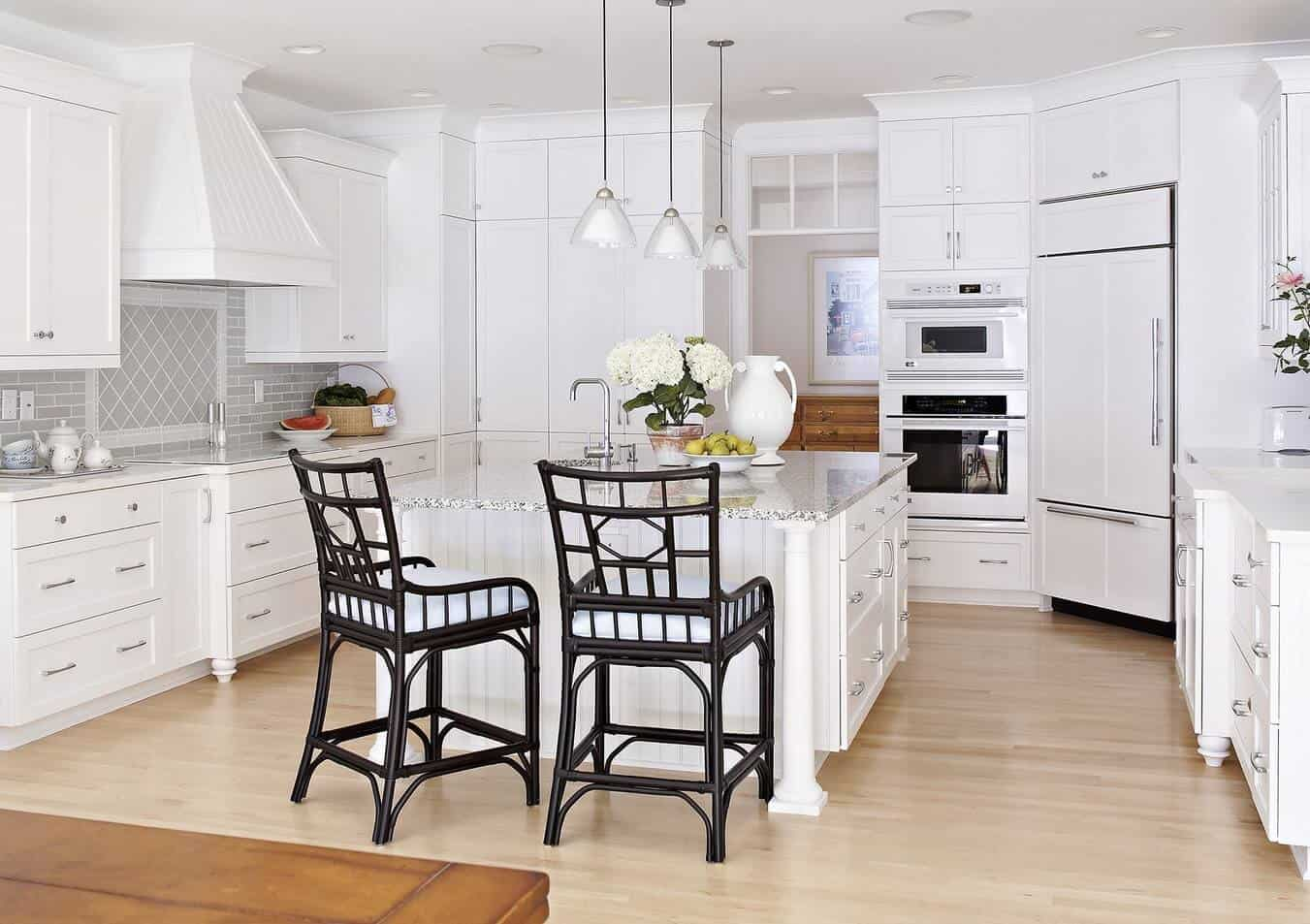 Beach style kitchen with a beadboard marble top breakfast island paired with black wooden chairs and surrounded with white appliances and cabinetry.