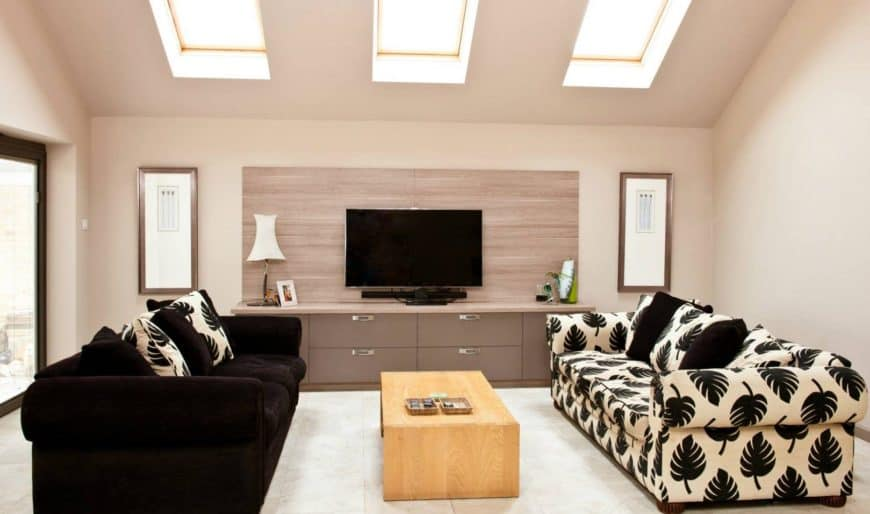Well lit living room features skylights and television mounted on the wooden panel. It has a light wood coffee table in between black and leaves patterned sofas.