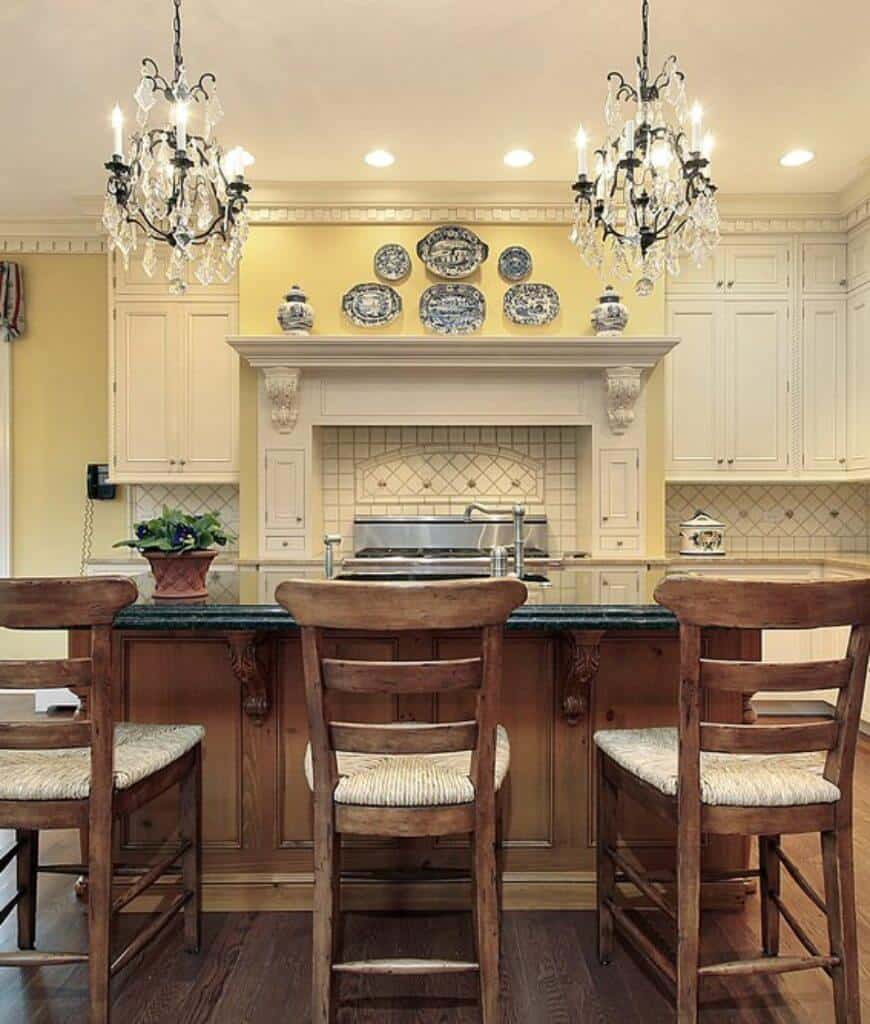 Fabulous kitchen designed with decorative ceramic plates and vases along with crystal chandeliers that hung over the wooden breakfast bar lined with cushioned chairs.