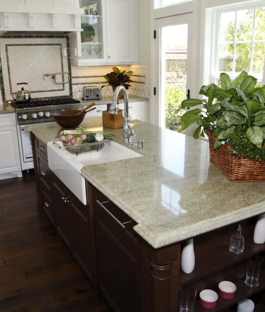 This kitchen features a dark wood breakfast island fitted with a white vessel sink and built-in shelving. There's a white range on the side along with cabinetry and gray marble countertop.