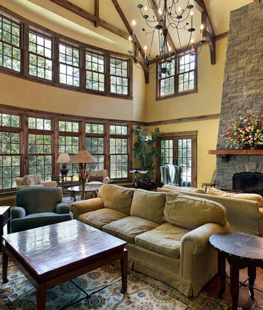 An airy living room offers a stone fireplace and multiple seating areas lighted by a candle chandelier that hung from the wood beam ceiling.