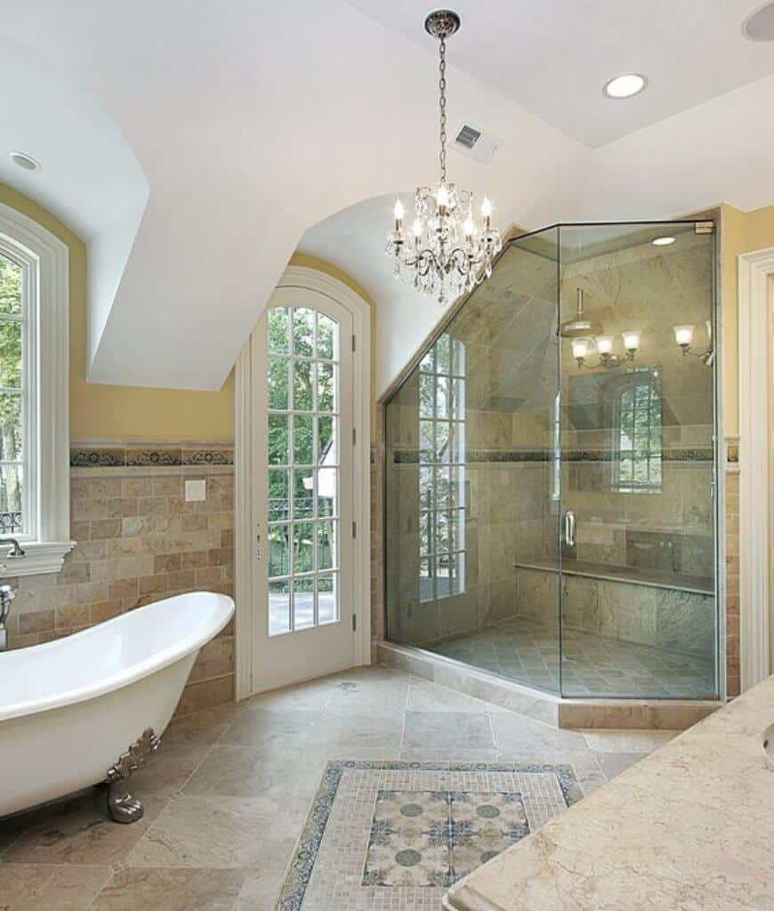 Airy master bathroom with a walk-in shower and clawfoot bathtub that sits next to the arched glass door leading to the balcony.