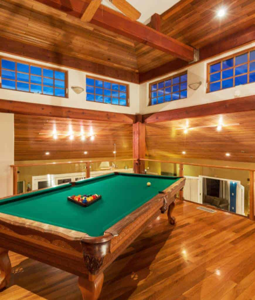 An all-wood room with glass railings and framed windows allowing natural light in. There's a pool table in the middle that sits on the rich hardwood flooring illuminated by recessed lights.