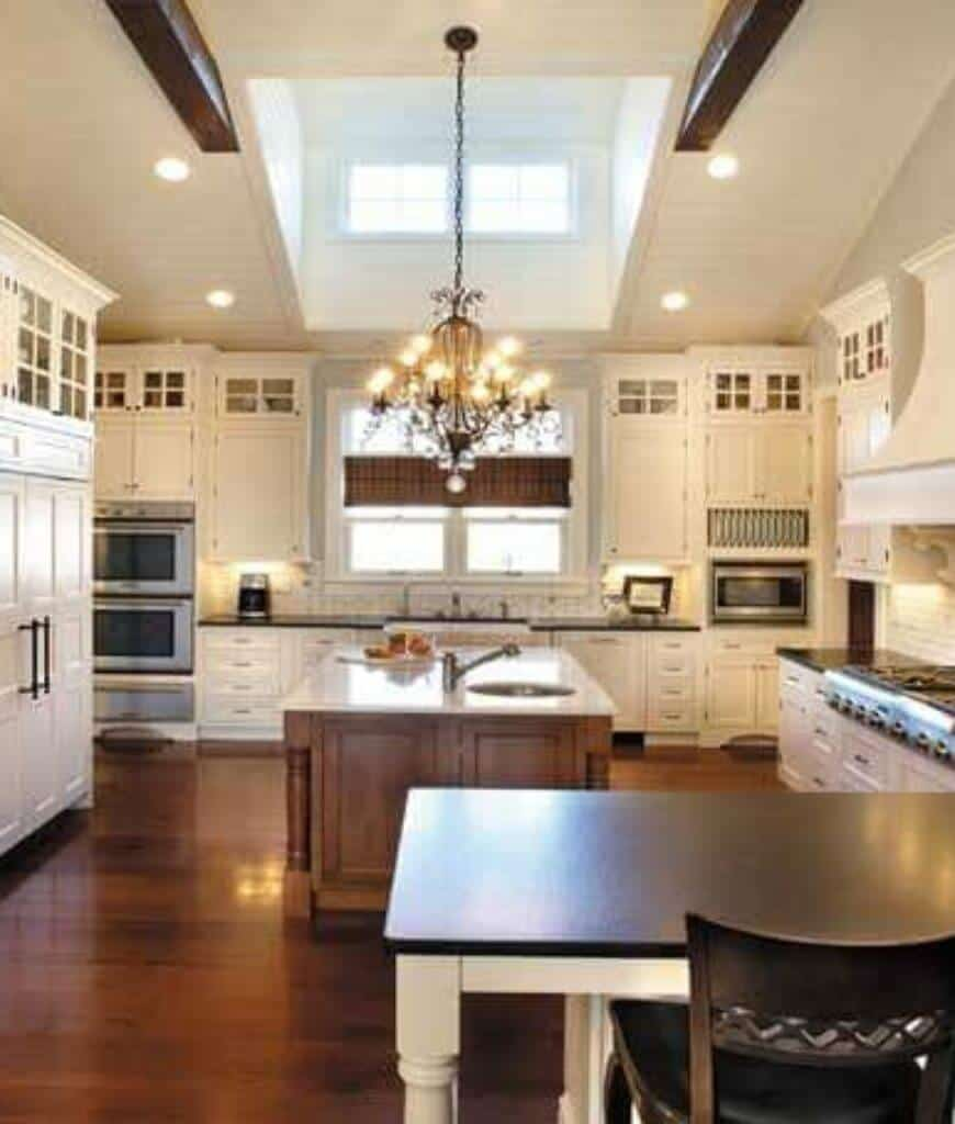 Traditional kitchen with a fancy chandelier and wooden central island surrounded by white cabinetry and glazed windows covered in brown valence.