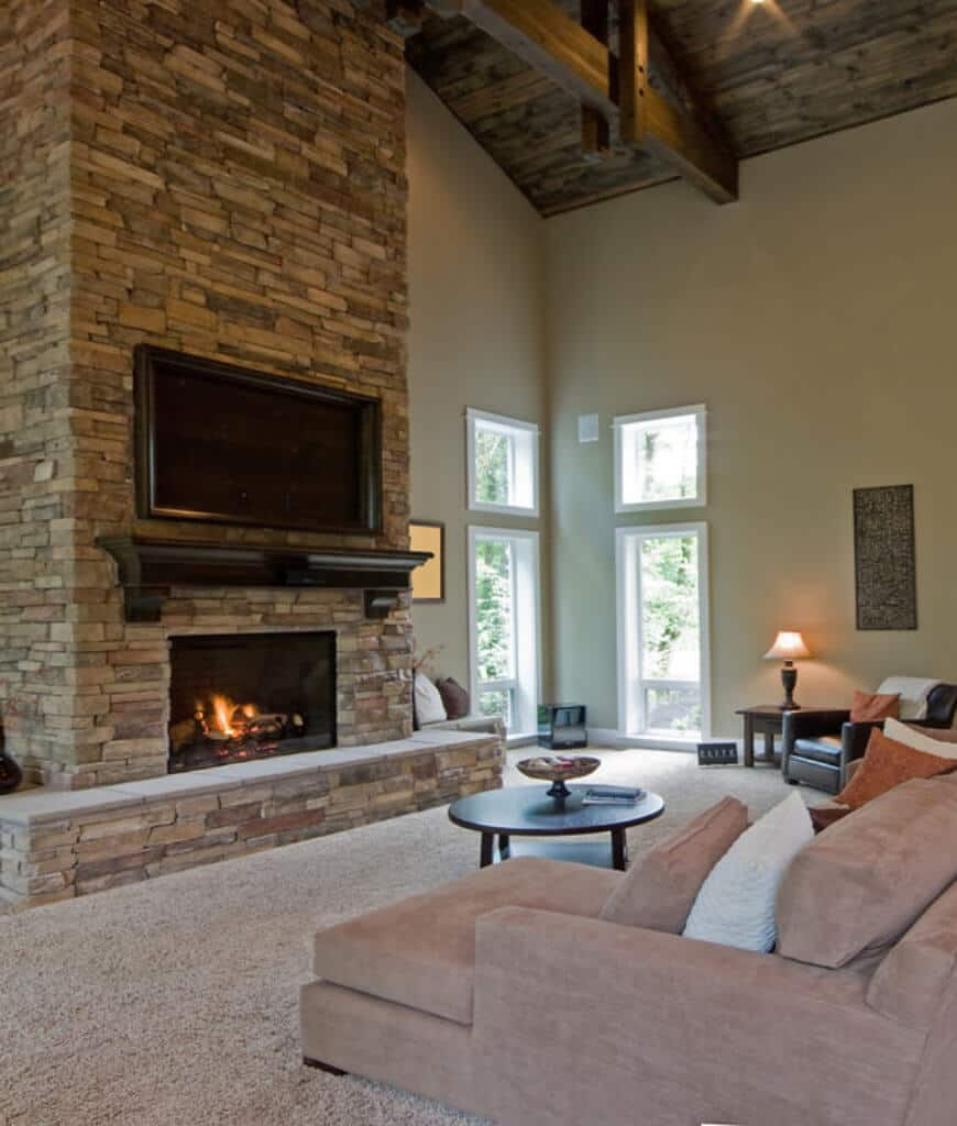 An L-shaped sofa faces the television and fireplace fitted on the stone brick pillar in this living room with carpet flooring and wood beam ceiling.