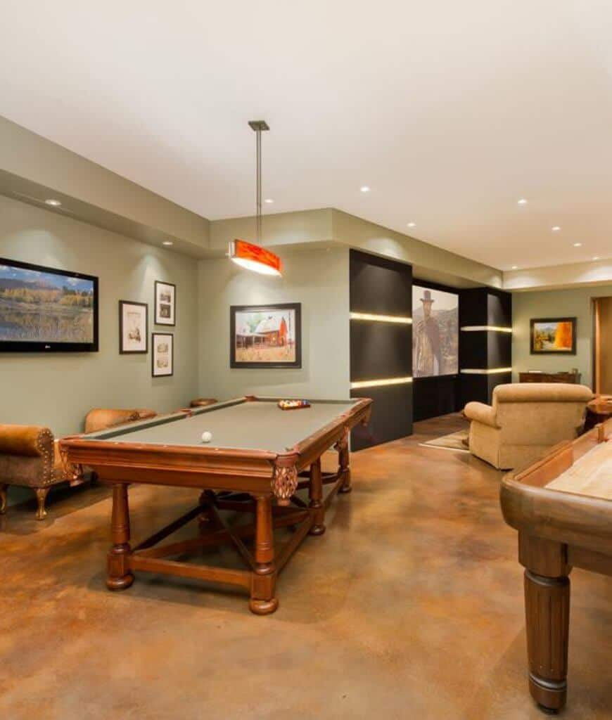 Well-lit entertainment room offers a comfy home theater setup and a farmhouse pool table accompanied by a Cleopatra chair and flat panel TV mounted on the gray wall.