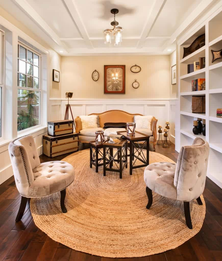 Traditional living room decorated with framed wall arts and various clocks mounted above the white wainscoting. It has a leather sofa and beige tufted chairs surrounding a modular coffee table that sits on an oval jute rug.