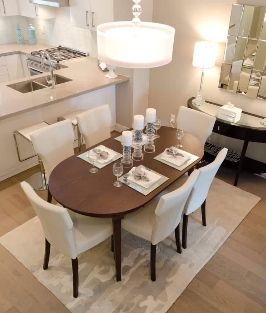 An open dining area with an oval dining table surrounded with white wingback chairs over a camo rug. It is lighted by a stylish drum pendant and table lamps that sit on a semi-circular console table.
