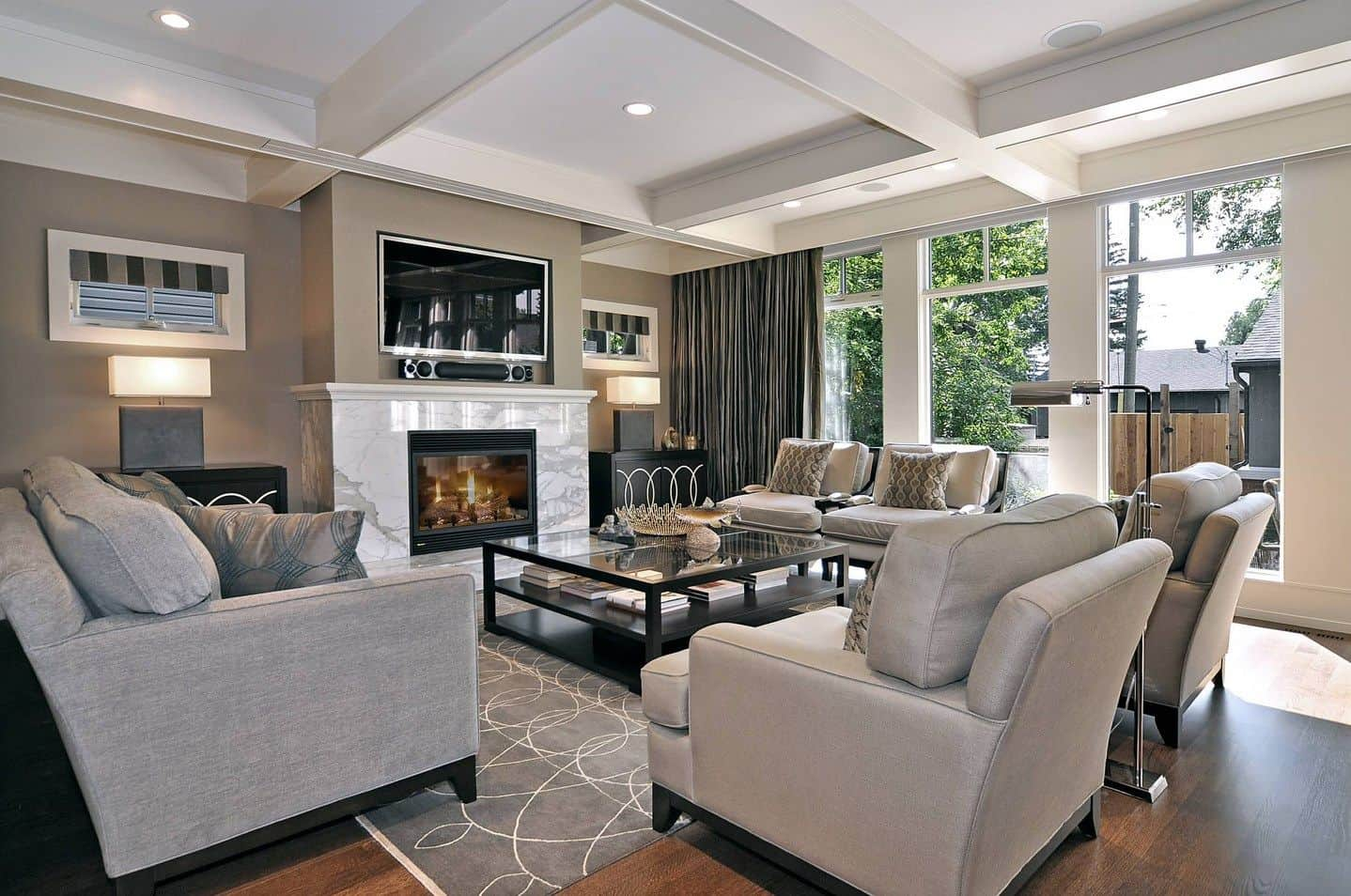Gray living room with coffered ceiling and hardwood flooring topped by a patterned rug. It includes dark wood tables with modern table lamps along with a fireplace and television in the middle.