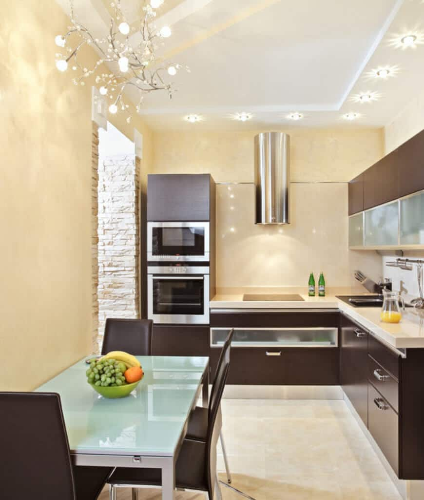 Stylish eat-in kitchen with smooth brown cabinetry that matches with the dining chairs surrounding a glass top table lighted by a glam chandelier.