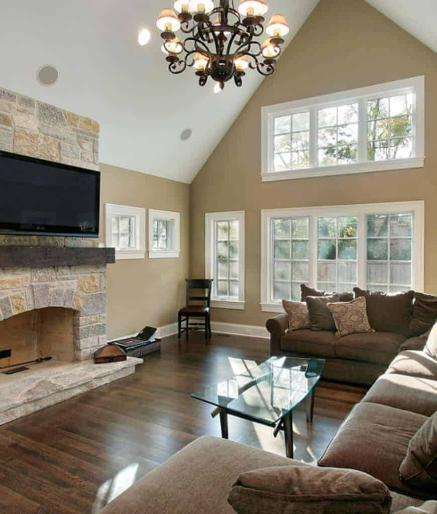 Beige living room with brown sectional and a glass top coffee table facing the stone fireplace lined with a rustic mantel. It is illuminated by a wrought iron chandelier that hung from the cathedral ceiling.