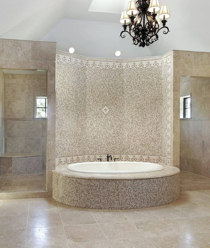 Marble tiled primary bathroom showcases a wrought iron chandelier and an elegant bathtub clad in mosaic tiles which makes it look stunning and sparkling when hit by light.