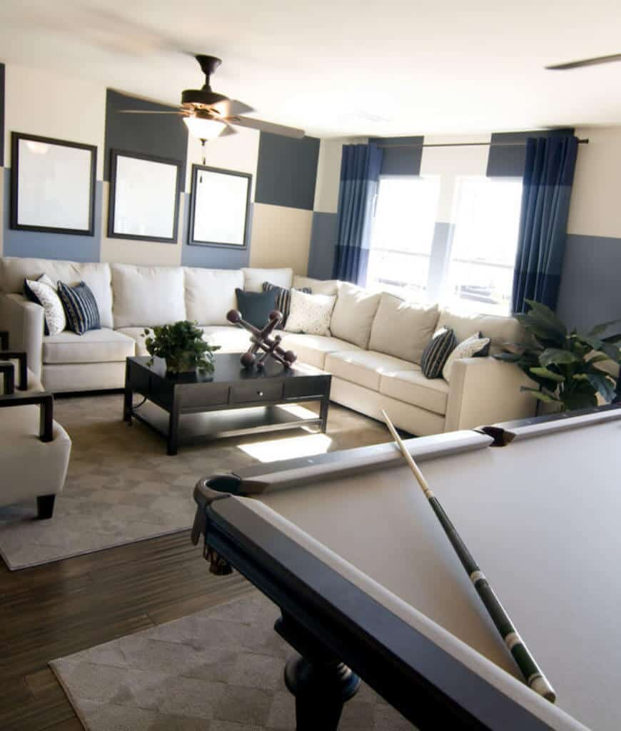 Bright man cave accented with checkered walls and blue draperies covering the glazed windows. It has a white sectional and a dark wood coffee table across the pool table on a diamond patterned rug.