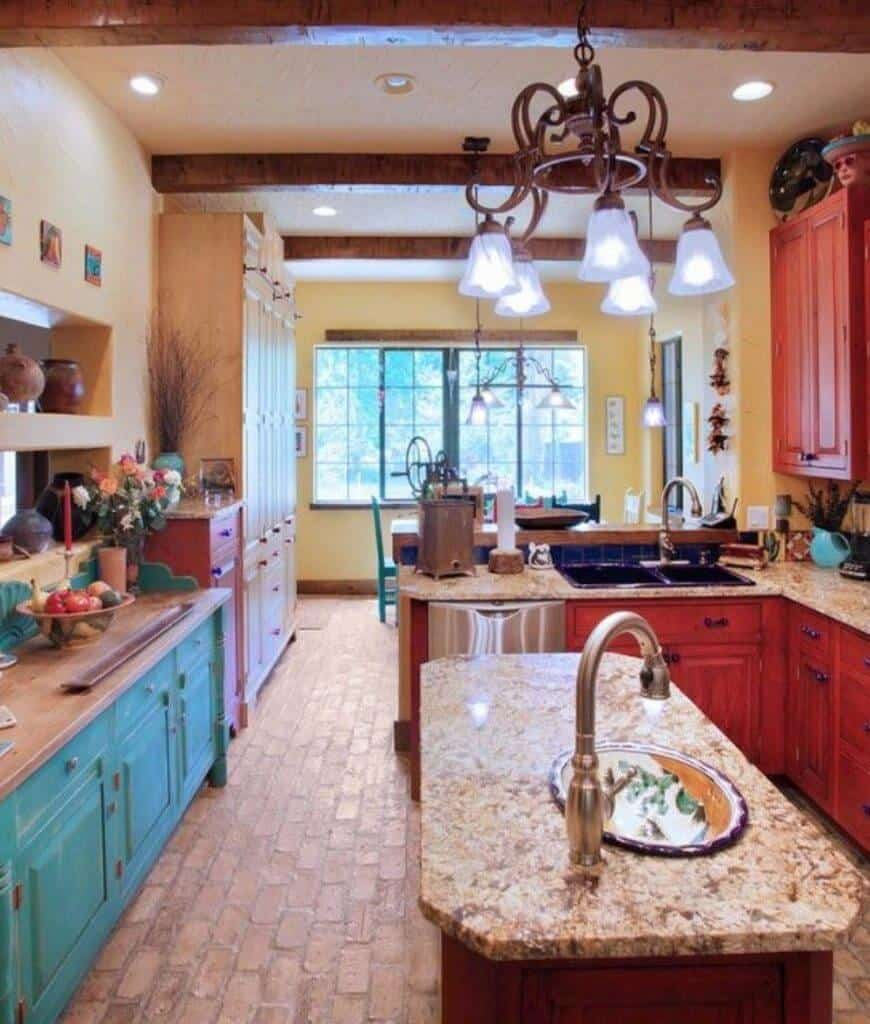 Southwestern kitchen features blue and red cabinetry that creates a nice striking contrast for a livelier look. It has brick flooring and wood beam ceiling mounted with recessed lights and chandelier.