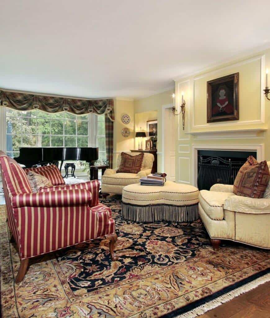 A lovely framed portrait hangs above the fireplace covered with a black metal fence in this living room with a red striped sofa and beige armchairs that sit on a tasseled vintage rug.