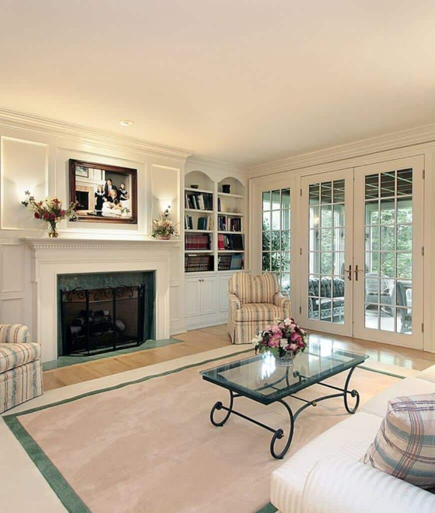 Classic white living room showcases a glass top coffee table and striped armchairs that complement with the pillow on a white sectional. It has a fireplace and a French door that leads to the patio.