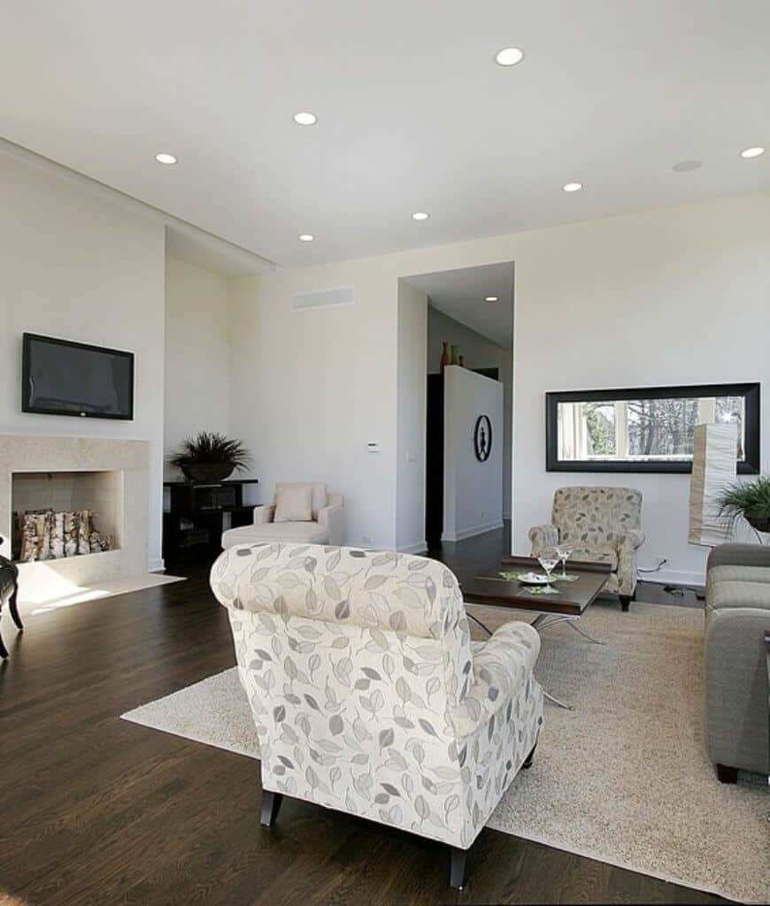 A flat panel TV hangs above the fireplace in this white living room with gray sectional and armchairs in leaves pattern.