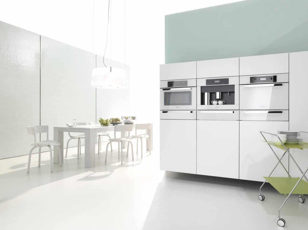 The sleek kitchen offers white modular appliances and modern dining space on the side illuminated by an oversized glass pendant.
