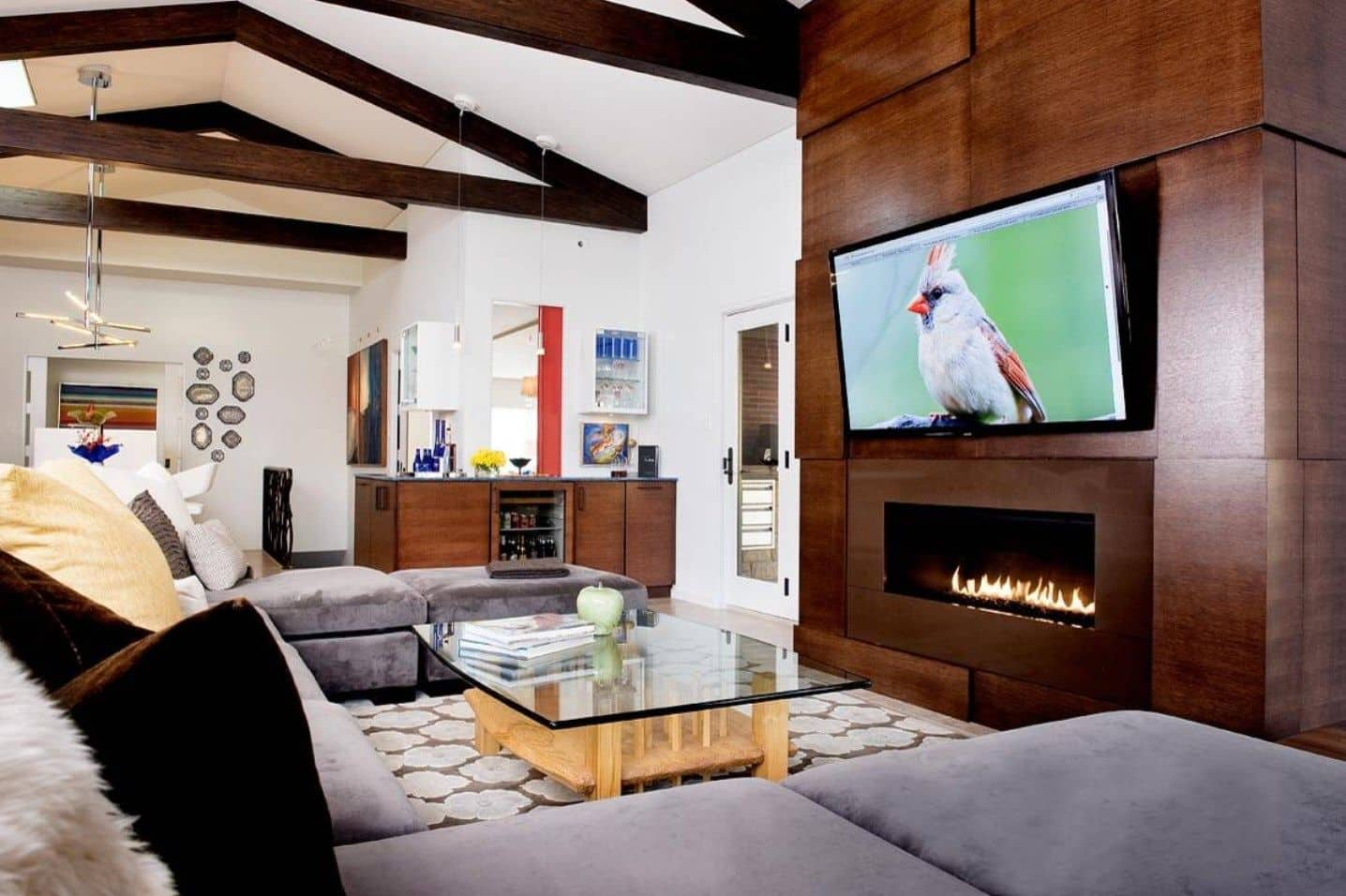 A U-shaped sectional with a glass top coffee table faces the huge television that's mounted above the fireplace in this living room with a vaulted ceiling.