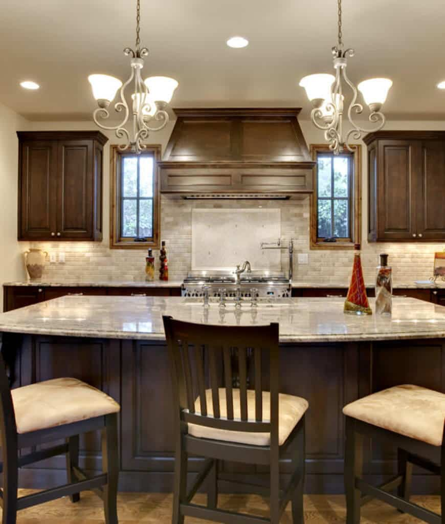 Ornate black chandeliers illuminate this kitchen offering a dark wood breakfast island paired with beige cushioned chairs and topped with gray marble counter complementing with the subway tile backsplash.