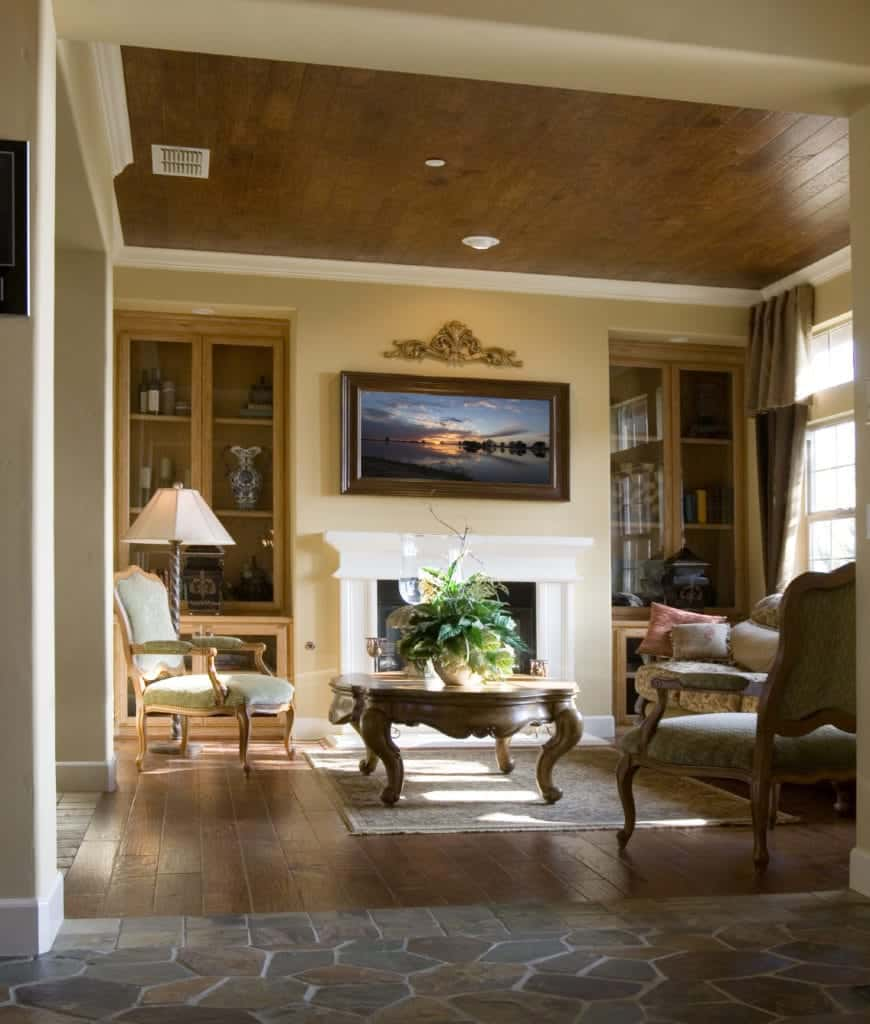 This living room showcases a wood plank ceiling and flooring bordered with flagstones and topped with a vintage rug. It has classy seats and a fireplace accented with a stunning landscape wall art.