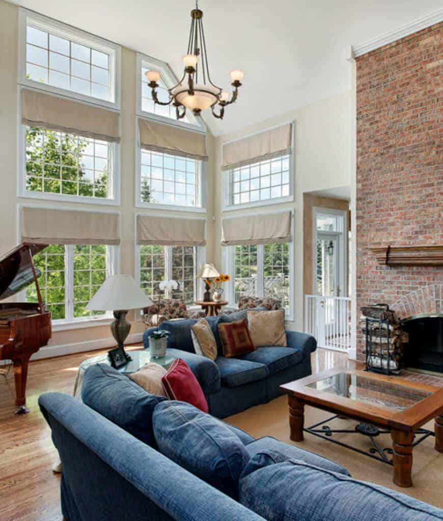 High ceiling living room features a brick fireplace and a wooden coffee table surrounded with blue sectionals. There's a seating area by the framed glass windows covered with beige roman shades.