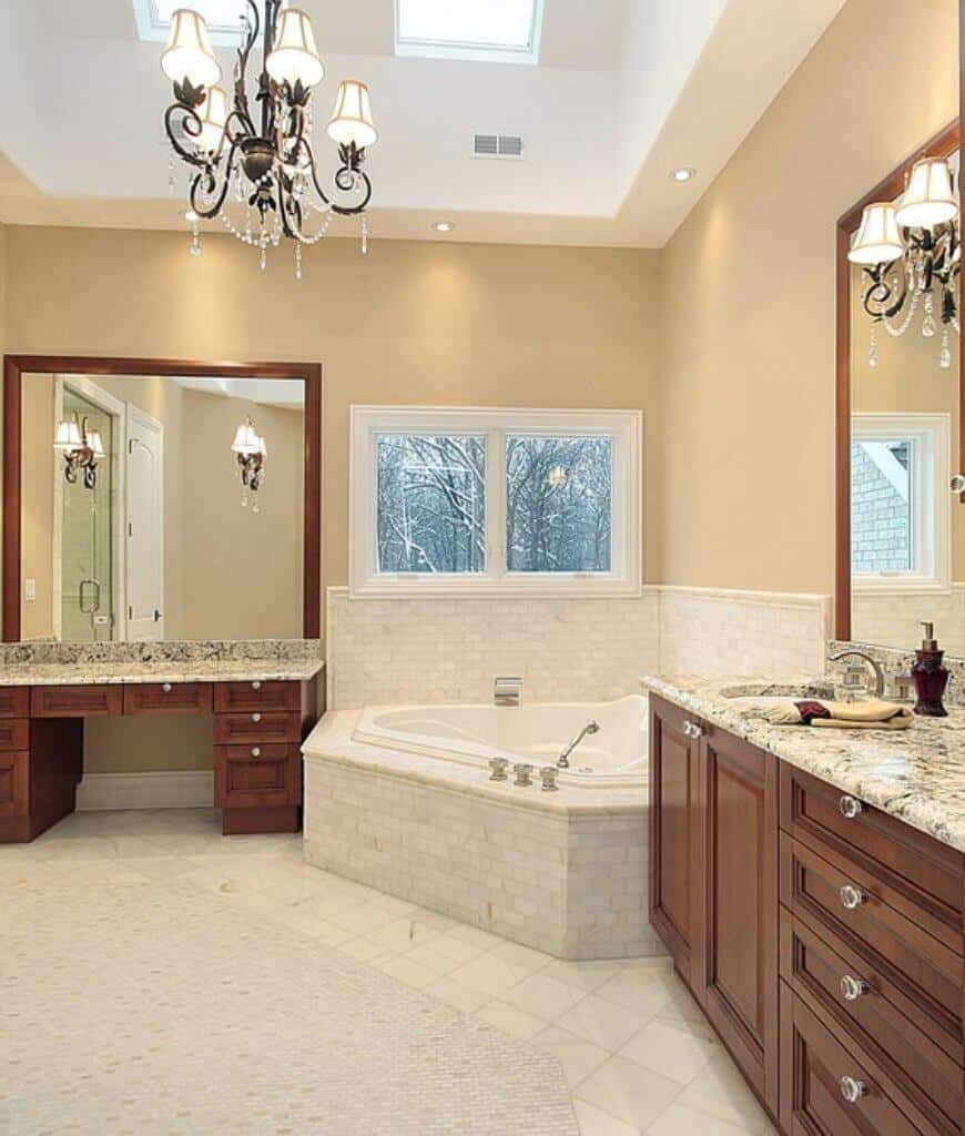 Beige master bathroom with a drop in bathtub in between wooden vanities topped with marble counters. It is lighted by a vintage chandelier wrapped in crystals and skylights fixed to the tray ceiling.