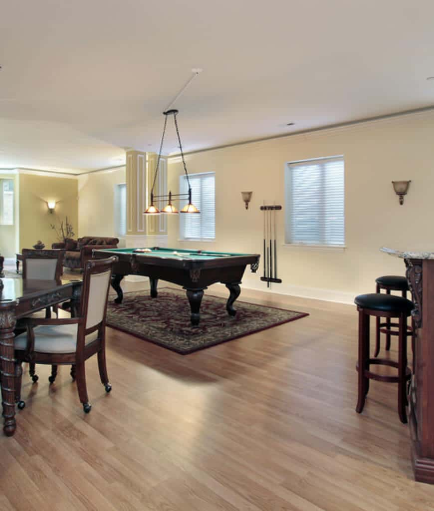 Yellow basement lined with wainscoted columns that serve as a separator from the living space and game area. It has a pool table that sits on a classic rug lighted by dome pendants.