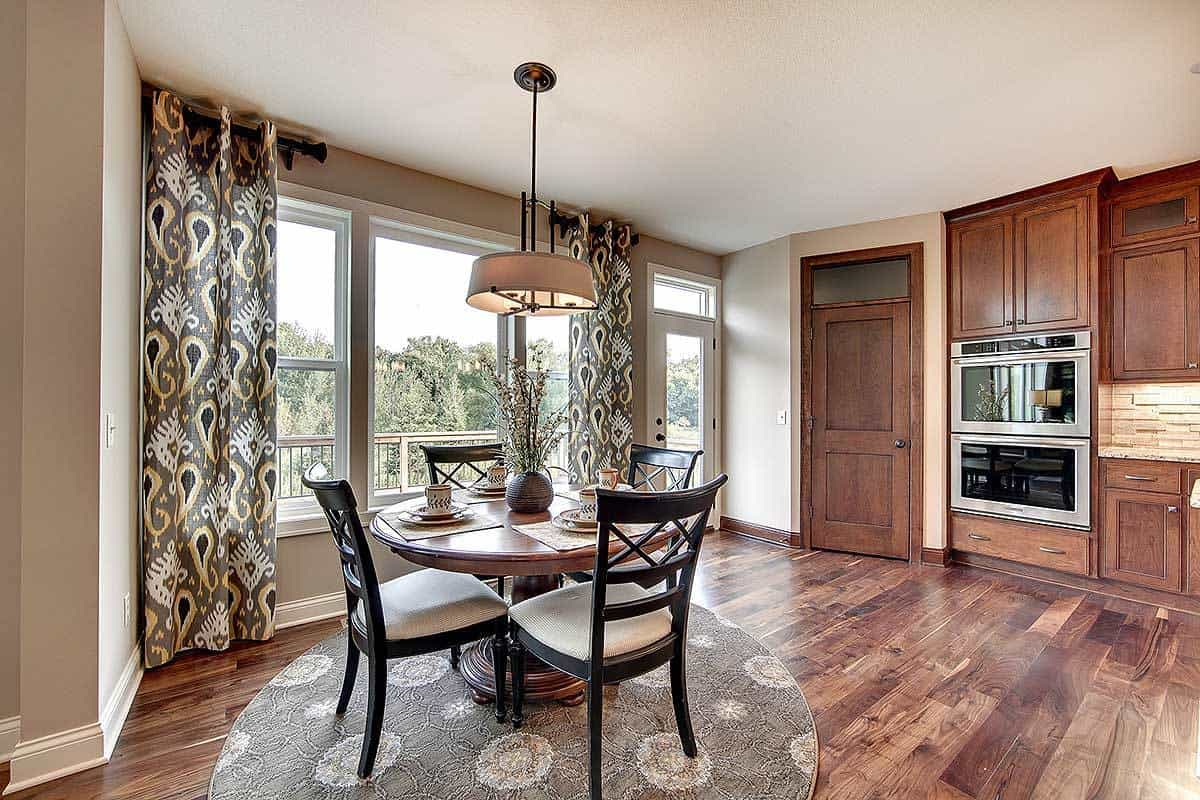The informal dining area beside the kitchen has a round wooden dining table surrounded by dark wooden chairs over a gray floral area rug that matches the curtains for a bit of homey touch.