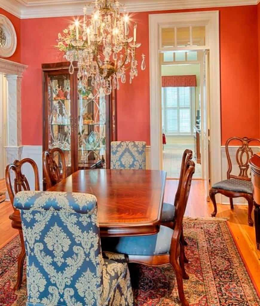 Charming dining room offers a display cabinet and wooden dining table paired with blue cushioned chairs and lighted by a fancy chandelier.