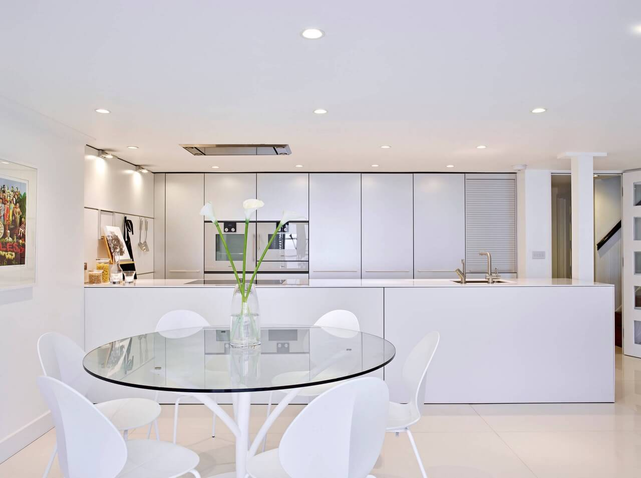 Gorgeous kitchen with sleek cabinetry and white appliances along with a round glass top dining table surrounded with contemporary chairs.