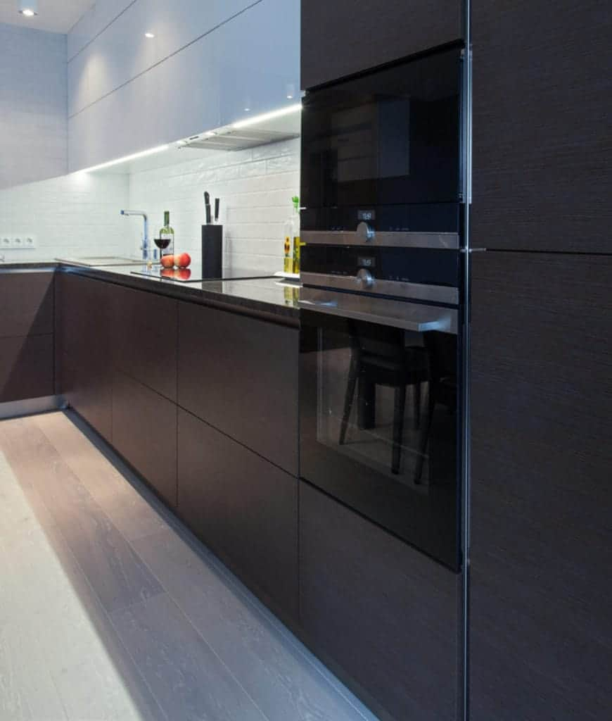 Black double wall oven is inserted into the dark wood cabinetry in this kitchen with white subway tile backsplash and white upper cabinets that create balance to the layout.