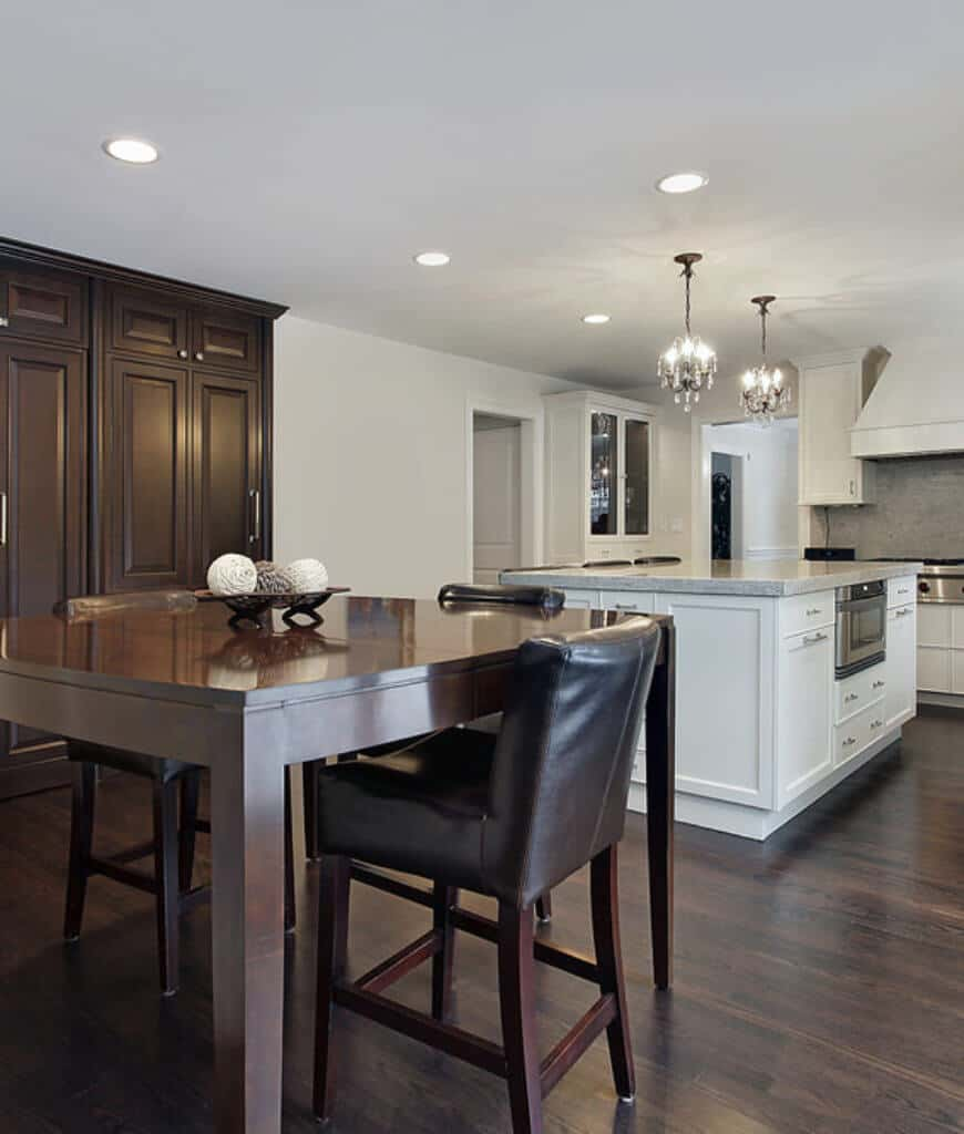 Eat-in kitchen with white cabinetry and central island contrasted with black leather chairs and a dark wood dining table that complements with the hardwood flooring.