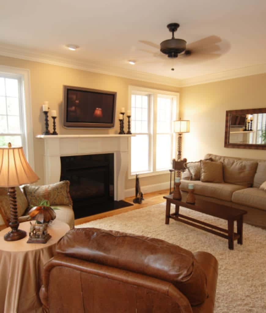 A flat panel TV hangs above the white fireplace in this living room with tan sectional and a rectangular coffee table along with brown leather and patterned armchairs with a round side table in the middle.
