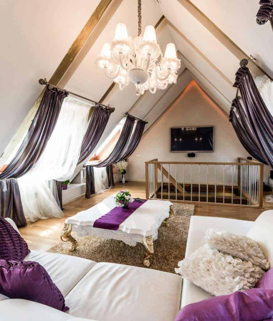 Attic living room accented with purple pillows and runner that lays on the elegant coffee table. It has a white chandelier and glazed windows covered with black and white sheer curtains.