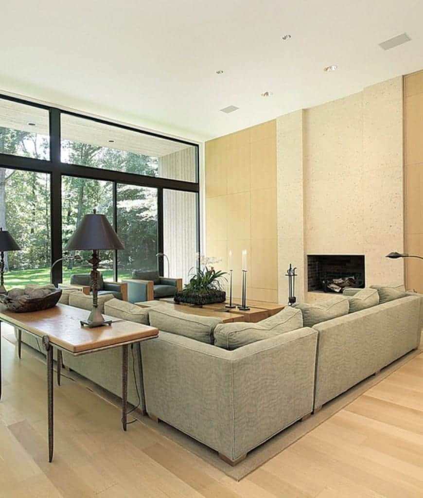 Well-lit living room showcases a sleek fireplace and L-shaped sectional filled with fluffy large pillows. It has light wood plank flooring and panoramic windows overlooking the lush green yard.