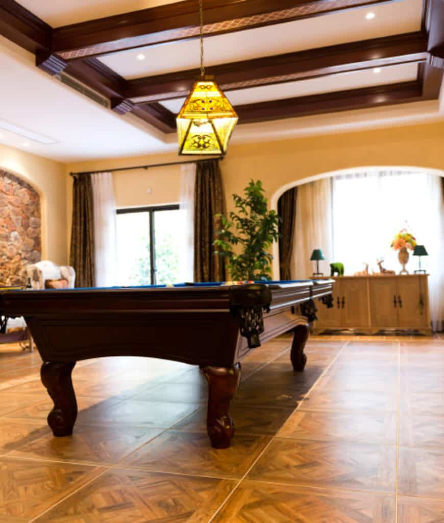 Mediterranean room features tiled flooring and wood beam ceiling with a hanging pendant light. There's a pool table in the middle surrounded by a wooden console table and cozy seats.