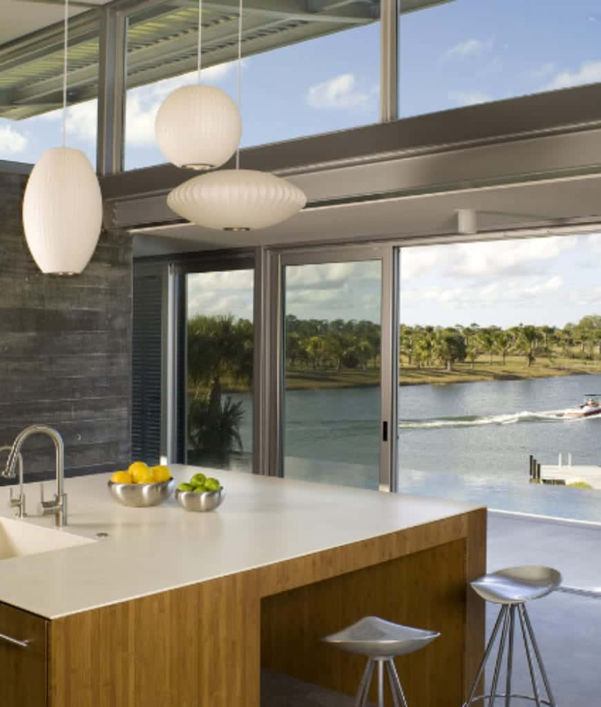 Various white pendants illuminate this kitchen showcasing a light wood breakfast island and panoramic windows overlooking a spectacular lake view.