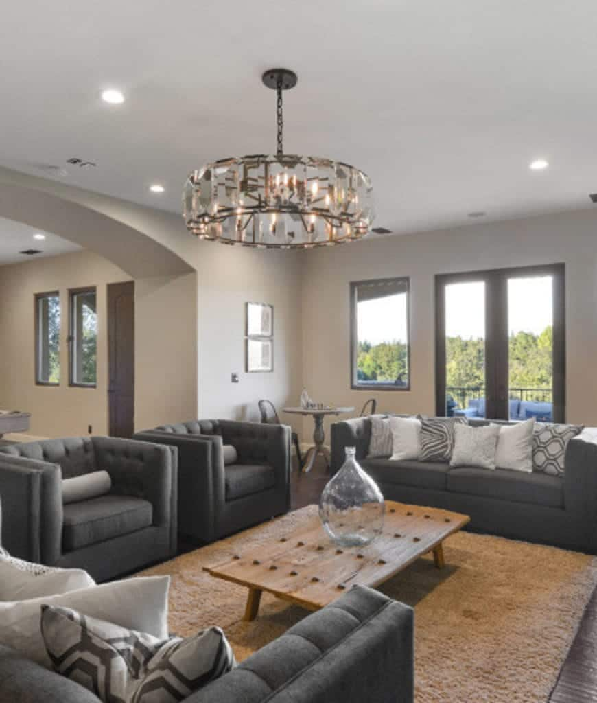 This living room features round chandelier and gray tufted seats along with a wooden coffee table topped by a glass bottle jar.