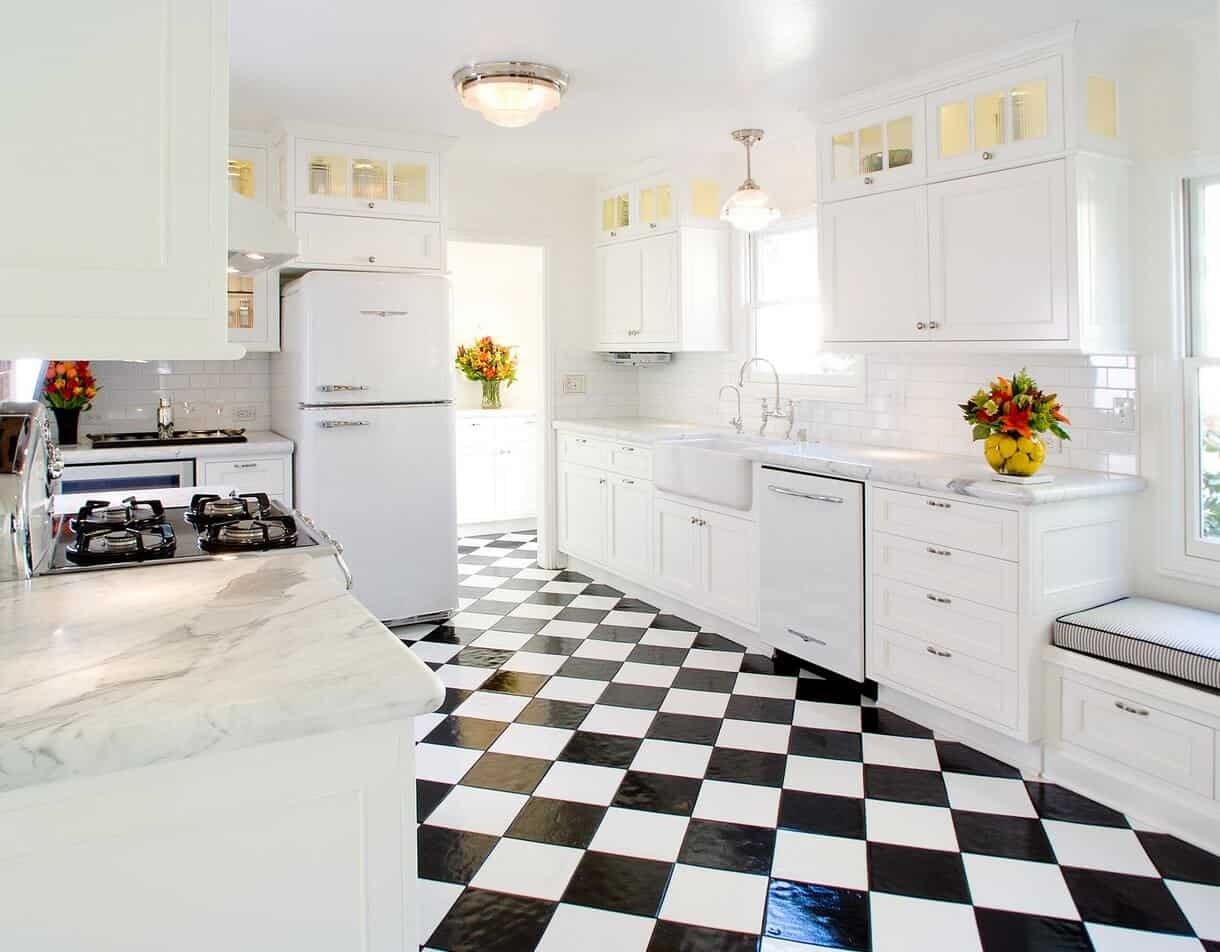 Classic white kitchen accented with a striking black checkered flooring lighted by a flush mount ceiling light. It has a white fridge and oven fitted along the cabinetry.