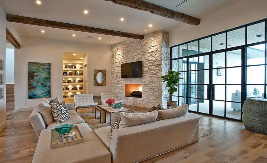Fresh living room boasts a stone brick accent wall mounted with a television and fireplace along with a beige ceiling fitted with recessed lighting and rustic wood beams.