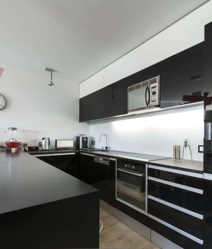 Black appliances camouflaged on the glossy cabinets in this sleek kitchen with white walls and natural hardwood flooring.