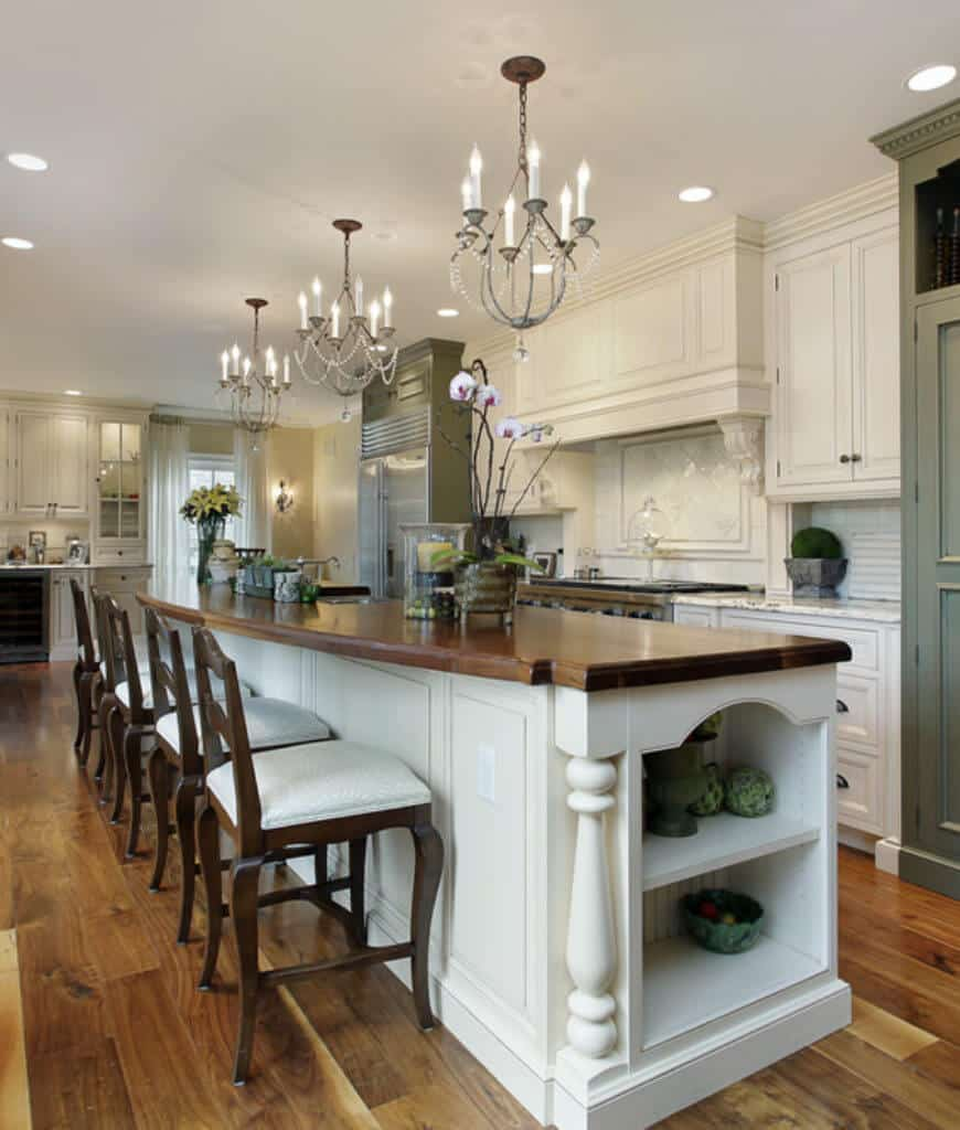 Gorgeous kitchen boasts a lengthy island bar lined with fabulous chandeliers and wooden counter chairs over wood plank flooring.