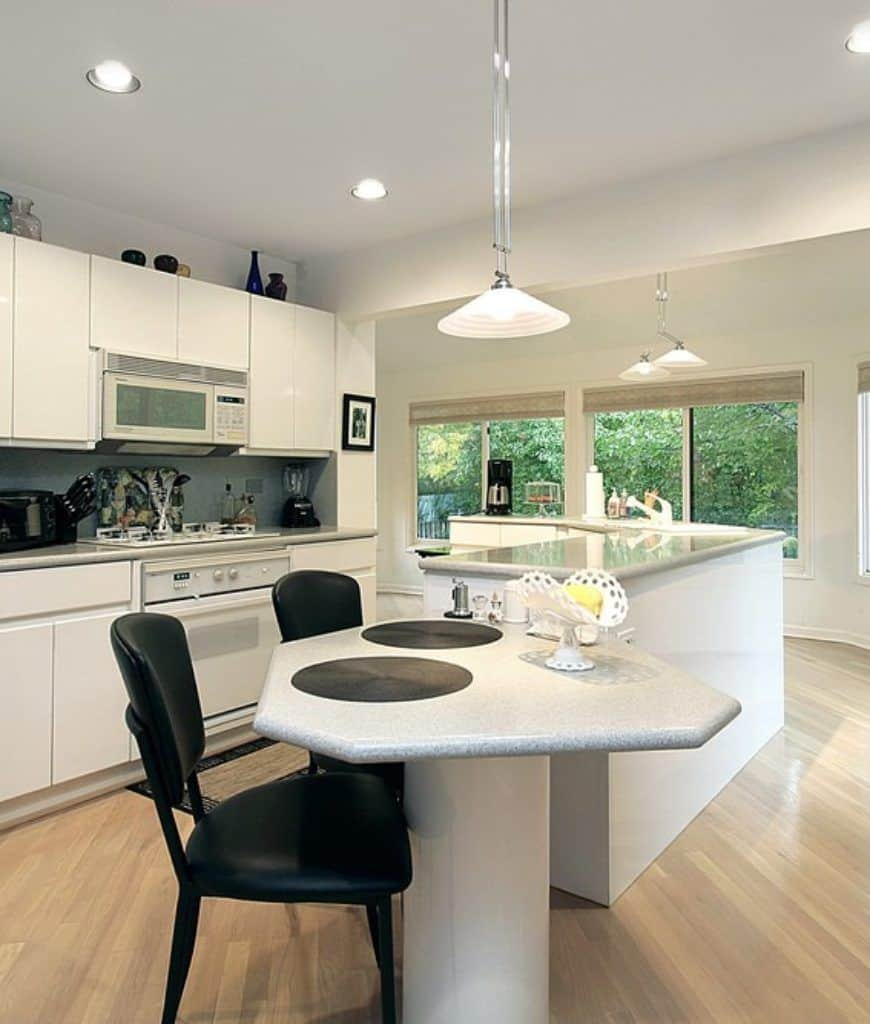 Modern kitchen showcases a curved island bar with an eating counter on its end that's accompanied by black leather chairs.
