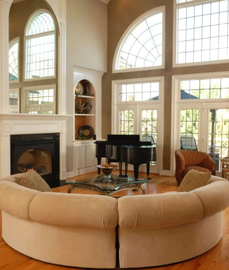 An airy living room offers a curved velvet sofa and glass top coffee table facing the fireplace that's topped with an arched mirror. There's a baby grand piano and coral round back chair by the framed glass windows overlooking the outdoor scenery.