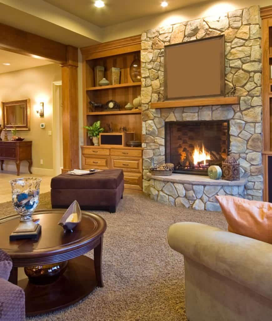 Cozy living room features a stone fireplace with built-in shelving on the side filled with vases and plant.